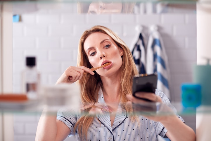 woman-brushing-teeth-looking-at-phone
