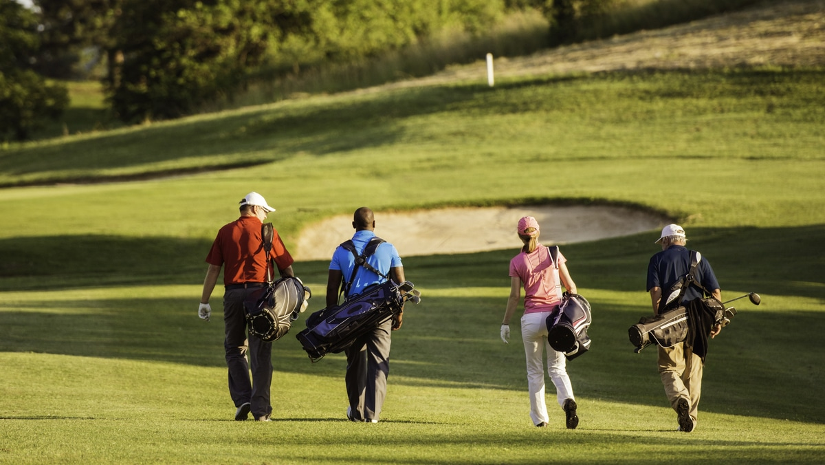 Four friends walking down a golf course together on their buddies trip
