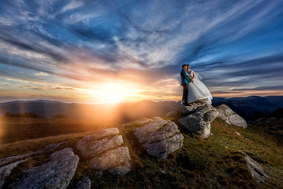 Just married couple standing on rocks with the sun setting over the mountains in the background